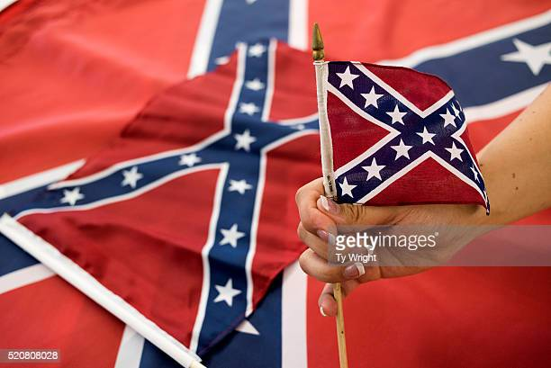 An employee holds up a Confederate flag during the manufacturing process at the Alabama Flag and Banner on April 12 2016 in Huntsville Alabama The...