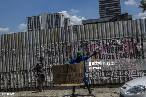An employee holds up a sign during a protest against the privatization of the State's water and sewage utility in front of Cia Esadual de Aguas e...
