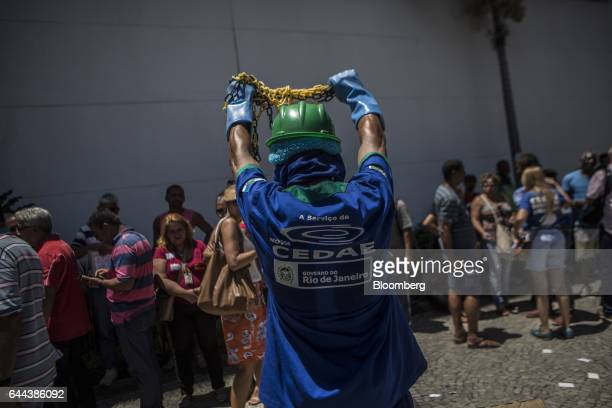 An employee holds up chains during a protest against the privatization of the State's water and sewage utility outside Cia Esadual de Aguas e Esgotos...