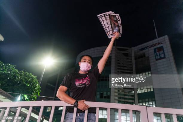 An employee holds up the latest copies of the Apple Daily newspaper as he stands on the gate at the offices on June 24, 2021 in Hong Kong, China....