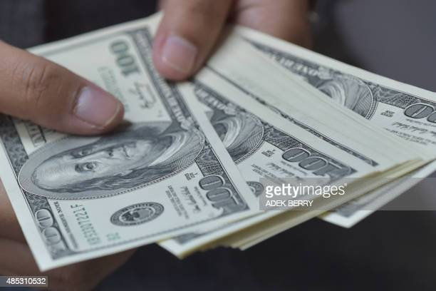 An employee holds US dollar banknotes at an Indonesian money changer's office in Jakarta on August 27 2015 Asian stocks surged August 27 after hints...