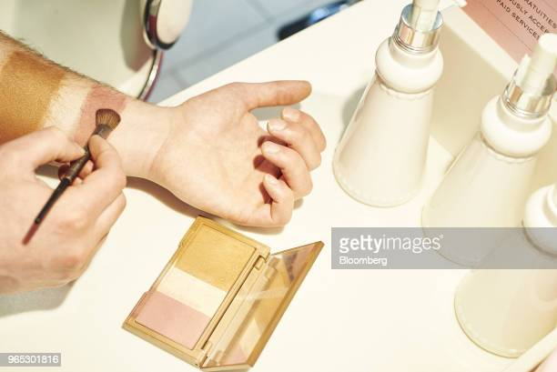 An employee illustrates a highlighting trio palette for a customer at an Ulta Beauty Inc store in New York US on Thursday May 31 2018 Ulta reported...