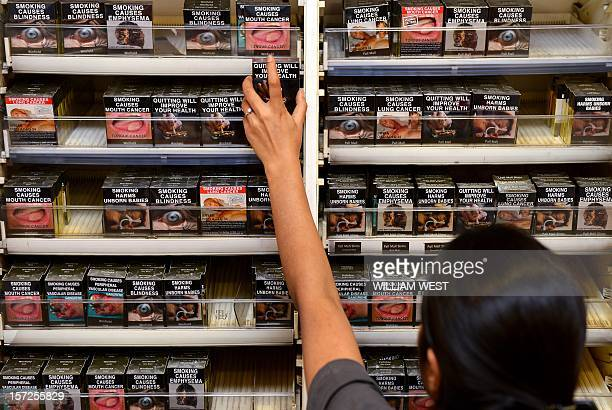 An employee in a bookshop adjusts packaged cigarettes which have to be sold in identical olivebrown packets bearing the same typeface and largely...