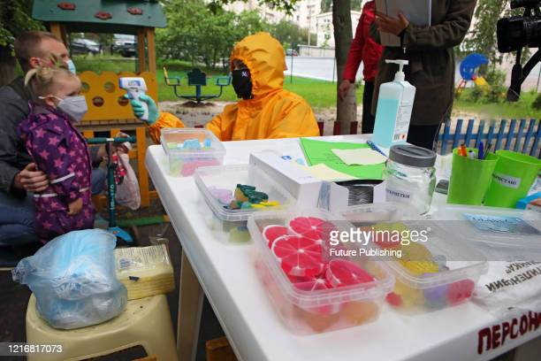 An employee in a hazmat suit takes girl's temperature with a contactless thermometer at a kindergarten which has reopened due to the easing of the...