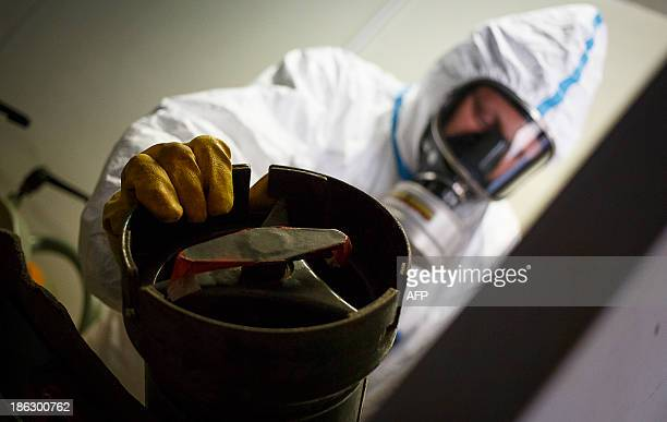An employee in protective clothing prepares to xray a dummy grenade during a demonstration in a chemical weapons disposal facility at GEKA in Munster...
