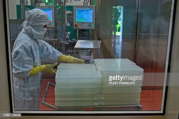 An employee in protective gear works on an assembly line for manufacturing vials of Covishield, AstraZeneca-Oxford's Covid-19 coronavirus vaccine at...