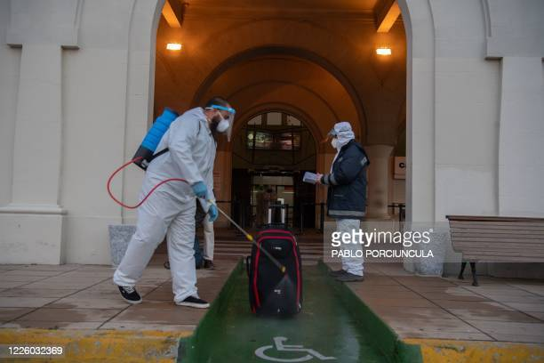 TOPSHOT An employee in protective suit disinfects a passenger's piece of luggage outside Argentinian ferry service company Buquebus' terminal in the...