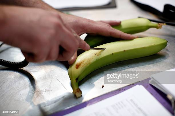 An employee inserts a temperature gauge into a Fyffes banana to check its quality during processing at Fyffes Plc's ripening and fruit distribution...