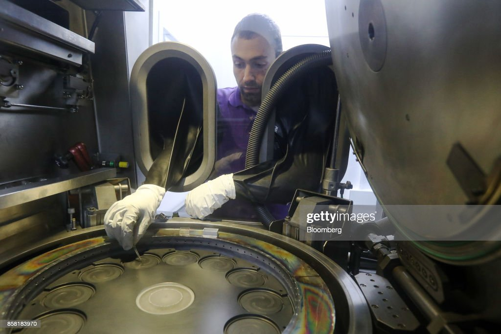 An employee inserts satellite location pins in to the base of the reactor to prepare the machine for the production of semiconductor wafer products at the IQE Plc headquarters in Cardiff, U.K., on Thursday, Sept. 28, 2017. IQE makes wafers that are needed for Vertical Cavity Surface Emitting Lasers (VCSELs), used for 3D sensors and widely thought to be included in the new iPhone. Photographer: Luke MacGregor/Bloomberg via Getty Images
