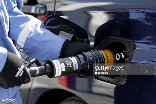 An employee inserts the nozzle of a hydrogen pump into a Toyota Motor Corp Mirai fuelcell vehicle during a demonstration at the Kawasaki Hydrogen...