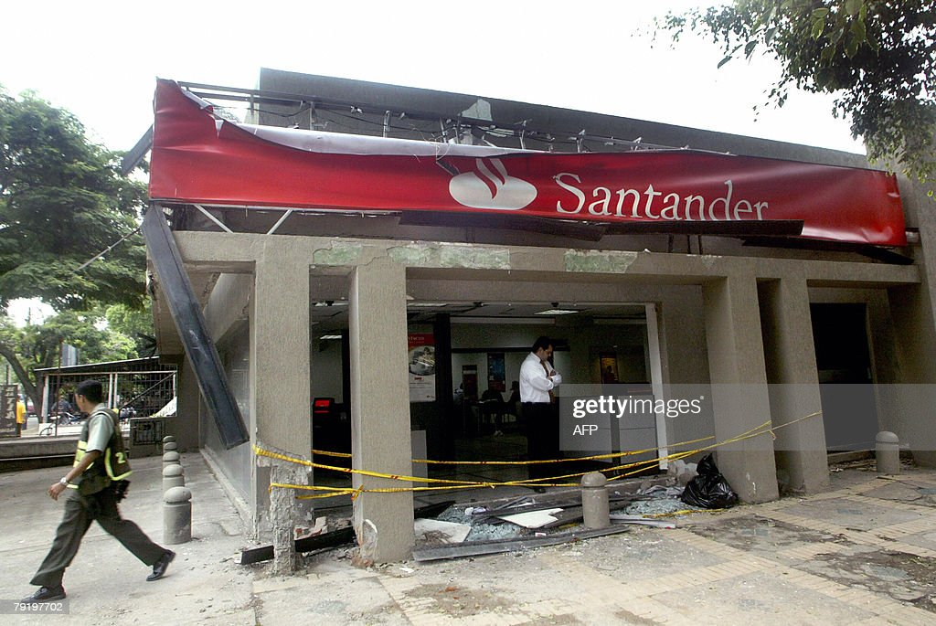 An employee inside a Bank Santander agency in Cali, Valle del Cauca department, Colombia, looks 24 January, 2008 the damage caused by an explosive artifact, allegedly set by the Revolutionary Armed Forces of Colombia (FARC) leftist guerrillas presumably as retaliation after some of their members were arrested on the eve, authorities said. AFP PHOTO/Carlos Julio MARTINEZ