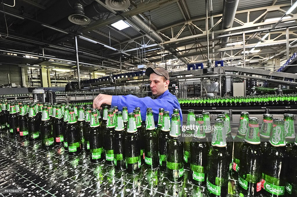 An employee inspect bottles of lager as they move along a conveyor belt at the Carlsberg A/S production plant in Kiev, Ukraine, on Wednesday, March 14, 2012. Sales in the Ukraine were 'significantly higher,' helped by better economic conditions and the recent introduction of premium beers, while the U.K. saw 'continuing strong growth,' the brewer said. Photographer: Vincent Mundy/Bloomberg via Getty Images