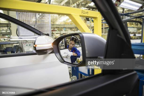 An employee inspecting a door handle is reflected in a rear mirror of a vehicle in the general assembly shop at the SAICGMWuling Automobile Co Baojun...