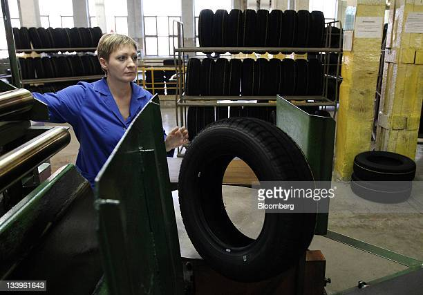 An employee inspects a car tire as it passes along the production line at the ZAO Sibur Holding tire manufacturing plant in Voronezh, Russia, on...