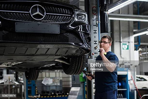 An employee inspects a CLA-class automobile on the production line at the Mercedes-Benz AG automobile plant, operated by Daimler AG, in Kecskemet,...