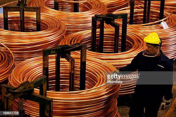 An employee inspects a coil of copper rod at the Luvata Malaysia Bhd plant in Pasir Gudang Johor Malaysia on Monday May 13 2013 At a time when copper...