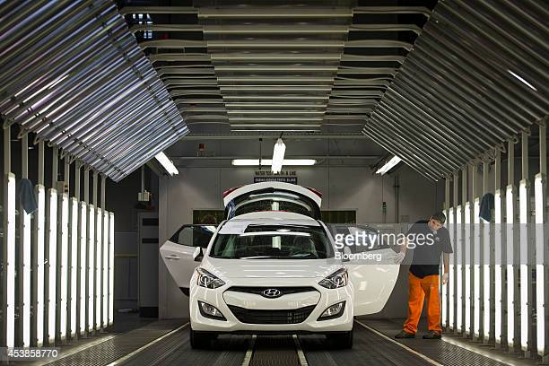 An employee inspects a completed ix30 automobile in a room illuminated by strip lighting at Hyundai Motor Co's plant in Nosovice Czech Republic on...