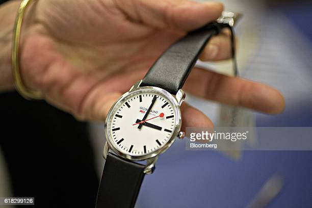An employee inspects a completed stop2go official Swiss Railways model wristwatch at the Mondaine Watch Ltd production facility in Solothurn...