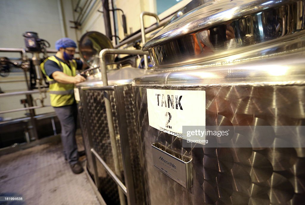 An employee inspects a distillation tank at the Treatt Plc flavoring and fragrances factory in Bury St Edmunds, U.K., on Wednesday, Sept. 25, 2013. Treatt Plc, the U.K. supplier of mango oil to the Body Shop, is considering the biggest investment splurge in its 127-year history as Chief Executive Officer Daemmon Reeve seeks to unshackle the company from family owned traditions. Photographer: Chris Ratcliffe/Bloomberg via Getty Images