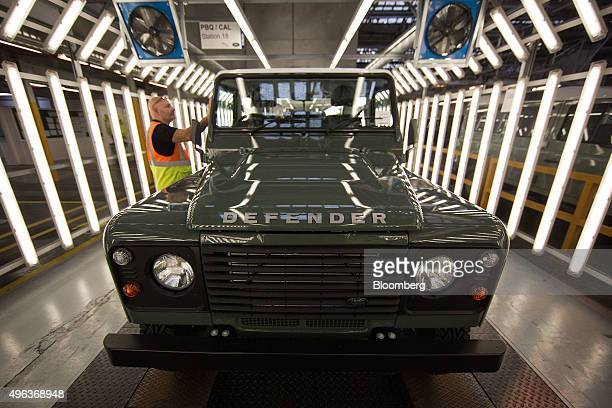 An employee inspects a door on a Land Rover Defender automobile as it moves down the inspection line at Tata Motors Ltd's Jaguar Land Rover vehicle...