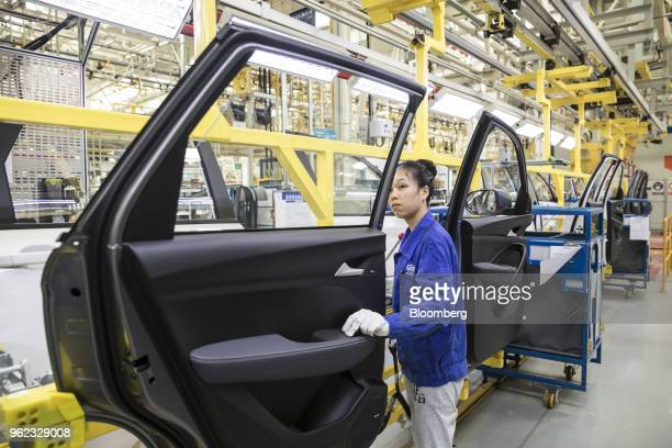 An employee inspects a door panel in the general assembly shop at the SAICGMWuling Automobile Co Baojun Base plant a joint venture between SAIC Motor...