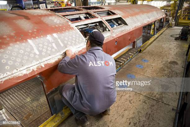 An employee inspects a Reseau Express Regional Paris express train carriage as it stands on the welding assembly line inside the Alstom SA railway...