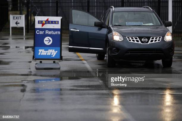 An employee inspects a returned vehicle at the Dollar Thrifty Automotive Group Inc lot inside the Louisville International Airport in Louisville...