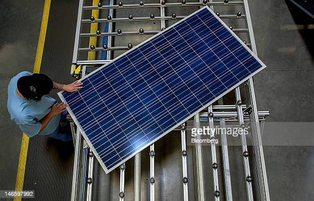 An employee inspects a solar panel on the production line at the Suntech Power Holdings Co Ltd facility in Goodyear Arizona US on Monday June 18 2012...
