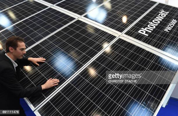 An employee inspects a solar panels system that directs itself automatically towards the sun presented by a French company at the InterSolar Europe...