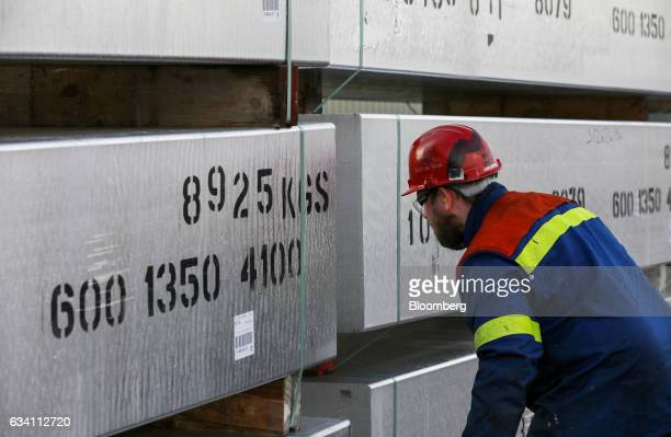 An employee inspects a stack of aluminum ingots stacked in a storage yard at the Lochaber aluminum smelter operated by Liberty House Group in Fort...