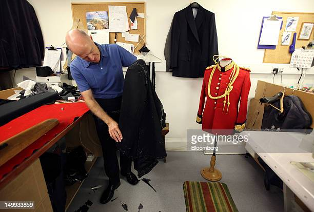 An employee inspects a suit in the workshop at the Gieves Hawkes store owned by Trinity Ltd on Saville Row in London UK on Tuesday Aug 7 2012 UK...