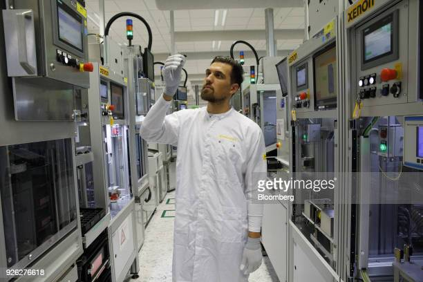 An employee inspects a Surround View camera lens on the automated driving technology production line at the Continental AG automotive factory in...
