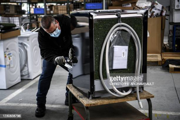 An employee inspects a washing-machine at the BSH electrical appliances company, a Back Market refurbishing company subcontractor, in...