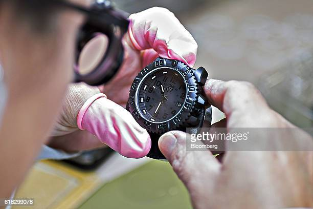 An employee inspects an assembled Luminox navy seal colormark 3050 series wristwatch at the Mondaine Watch Ltd production facility in Solothurn...