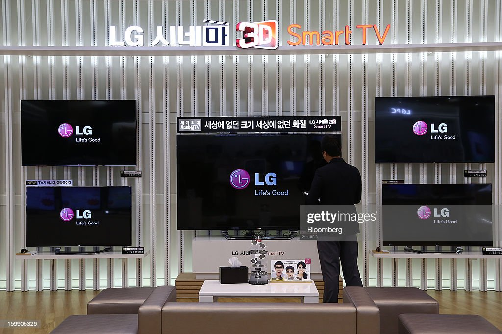 An employee inspects an LG Electronics Inc. Cinema 3D television using LG Display Co. panels at the company's flagship store in Seoul, South Korea, on Tuesday, Jan. 22, 2013. LG Display Co., the world's second-largest maker of flat panels, is scheduled to release fourth-quarter earnings on Jan. 24. Photographer: SeongJoon Cho/Bloomberg via Getty Images