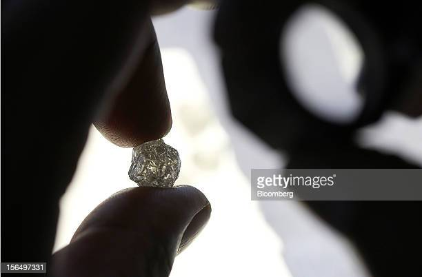 An employee inspects an uncut diamond at DTC Botswana a unit of De Beers in Gaborone Botswana on Thursday Oct 25 2012 De Beers the biggest diamond...