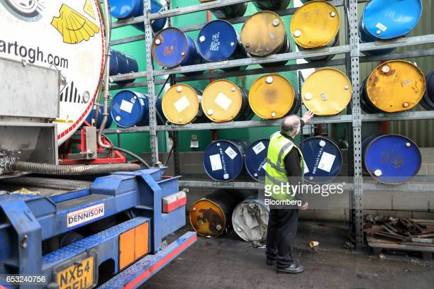 An employee inspects barrels of refined oil and lubricant additives in the storage yard at Rock Oil Ltd's factory in Warrington UK on Monday March 13...