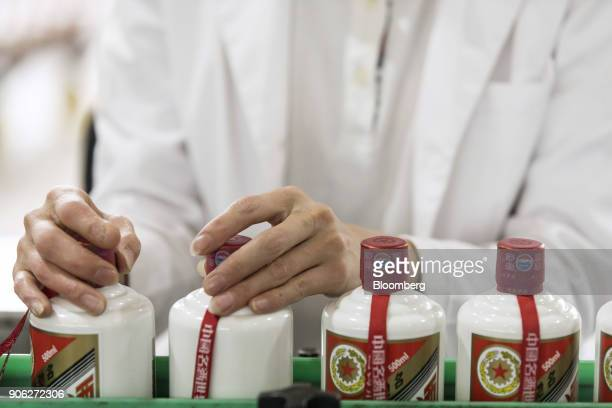 An employee inspects bottles of Moutai baijiu on the production line at the Kweichow Moutai Co factory in the town of Maotai in Renhuai Guizhou...
