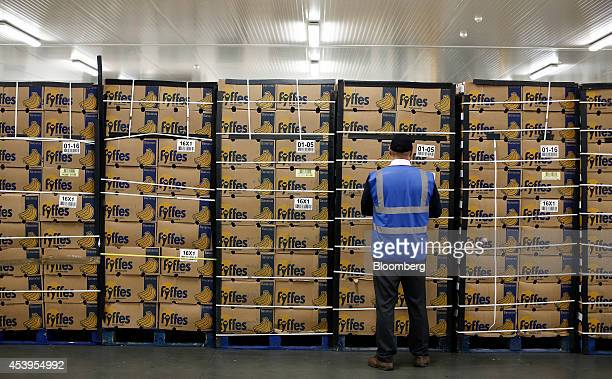 An employee inspects boxes of ripe Fyffes bananas stored ahead of shipping from Fyffes Plc's banana ripening and fruit distribution plant in...
