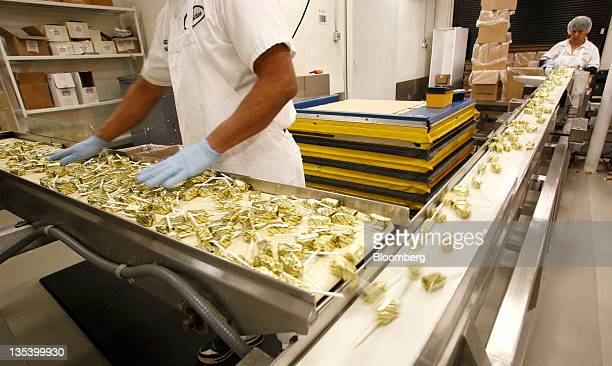 An employee inspects butterscotch lollipops moving on a conveyor belt before being packaged at the See's Candies Inc. Lollipop factory in Burlingame,...