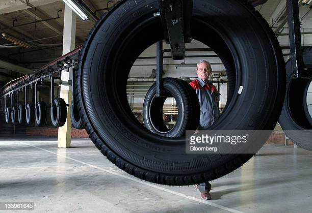 An employee inspects car tires as they pass along the production line at the ZAO Sibur Holding tire manufacturing plant in Voronezh, Russia, on...
