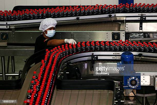 An employee inspects labels on bottles of CocaCola soda as they move along the production line at the CocaCola Co bottling plant in Hmawbi Myanmar on...