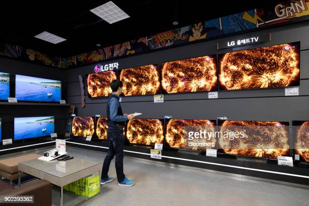 An employee inspects LG Electronics Inc curved organic lightemitting diode televisions at an EMart Inc Electro Mart store in Gimpo South Korea on...