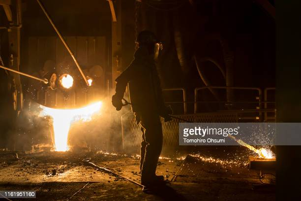 An employee inspects molten steel from an electric arc furnace on the production line of the Jonan Steel Corp factory on July 14 2019 in Kawaguchi...