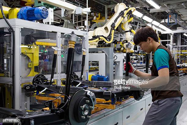 An employee inspects rear axles for Hyundai Motor Co. Elantra vehicles and Ioniq electric vehicles on the production line at the company's plant in...