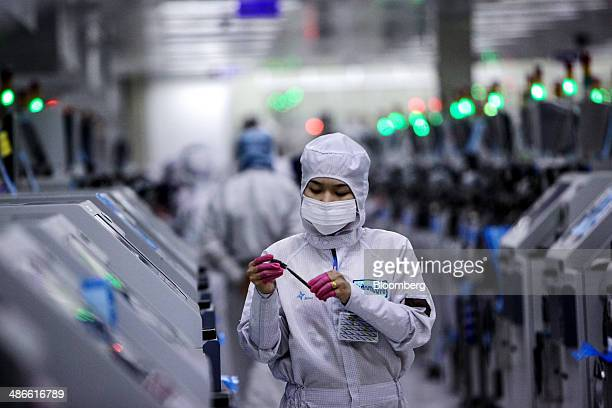 An employee inspects semiconductor chips on the production line at the Hana Microelectronics Pcl plant at the HiTech Industrial Estate in Bang PaIn...