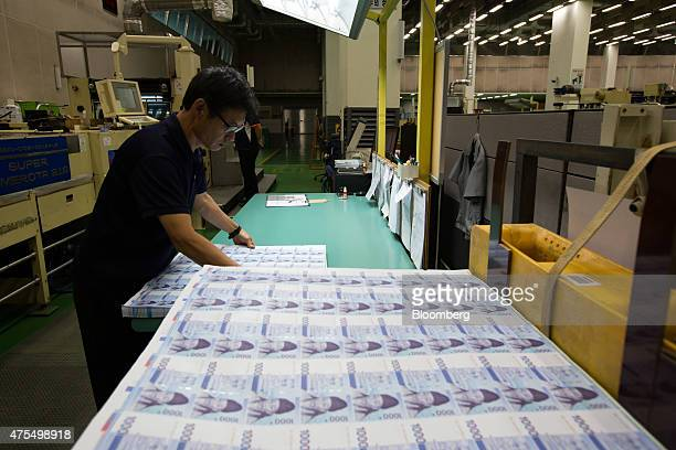 An employee inspects sheets of South Korean 1000 won banknote at the Korea Minting Security Printing ID Card Operating Corp factory in Geyongsan...