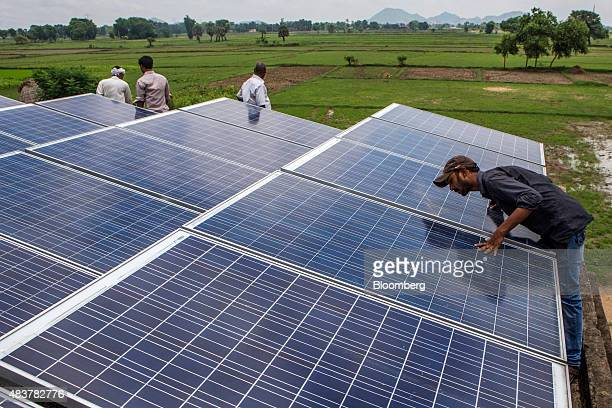 An employee inspects solar panels part of a solar power microgrid in the village of Dharnai in Jehanabad Bihar India on Thursday July 9 2015 While...