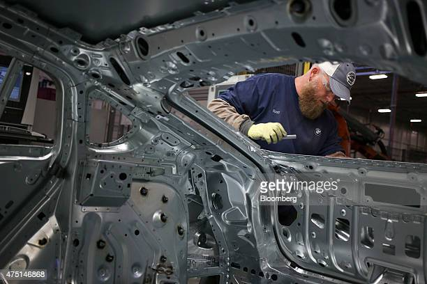 An employee inspects the body frame of a Bayerische Motoren Werke AG X4 sports utility vehicle on the assembly line at the BMW Manufacturing Co...
