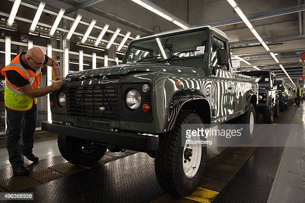 An employee inspects the bonnet of a Land Rover Defender automobile as it moves down the inspection line at Tata Motors Ltd's Jaguar Land Rover...